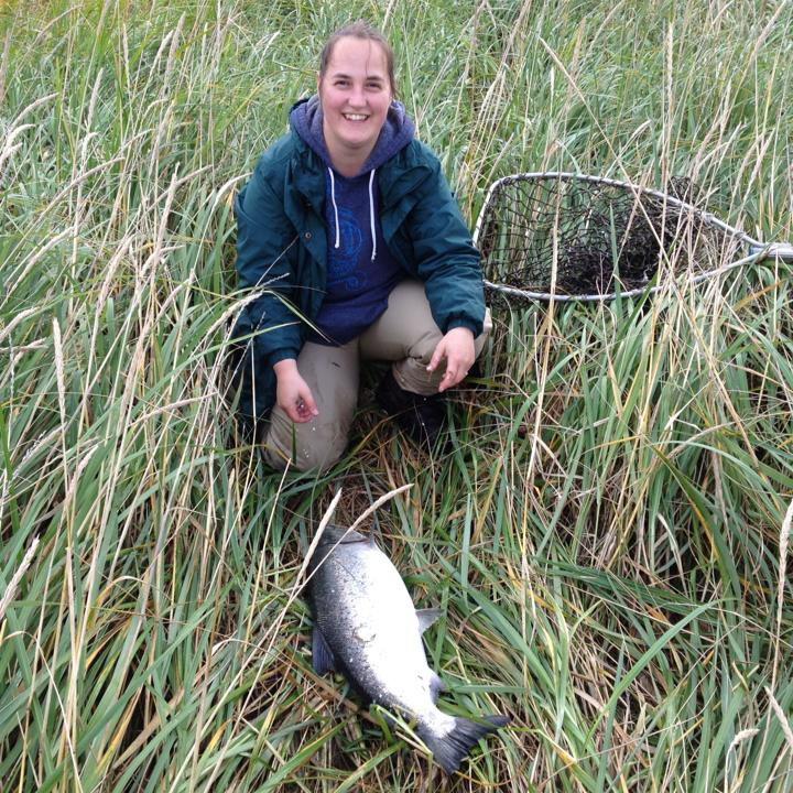 Peggy Azuyak in tall grass with a salmon