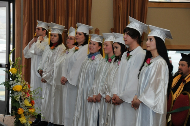 Students in white caps and gowns standing in a graduation ceremony